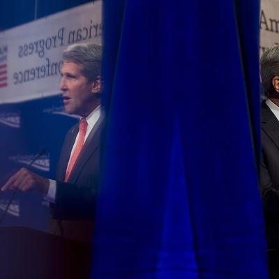 John Kerryn kuvassa näkyy myös hänestä muovipleksin kautta muodostuva heijastus sinisen verhon vasemmalla puolella.