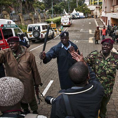 Poliisi ja sotilaat yrittävät työntää lehtimiehiä kauemmaksi ostoskeskuksella, jossa piiritys jatkuu.