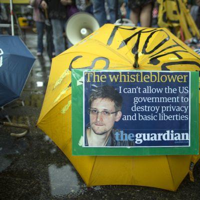 Snowden-juliste mielenosoittajan sateenvarjossa