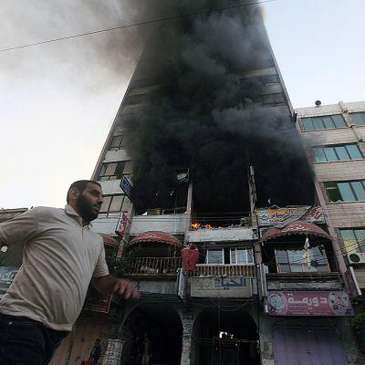 Ihmiset juoksivat turvaan Israelin ilmavoimien iskettyä Al Shoroq -rakennukseen.