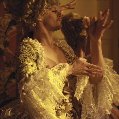 Barokkiajan naisten mekkoon pukeutunut miesnäyttelijä