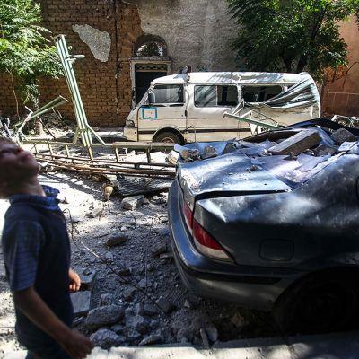 Poika katselee taivaalle vaurioituneiden autojen vierellä