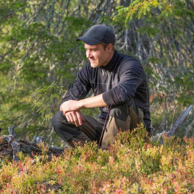 Juha-Pekka Paananen katselee metsässä kuukkelia.