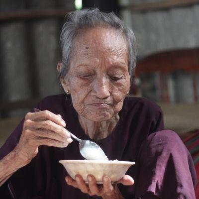 Riippumatossa istuva vanha nainen pitelee puurokuppia kämmenellä ja ottaa puuroa lusikkaan.