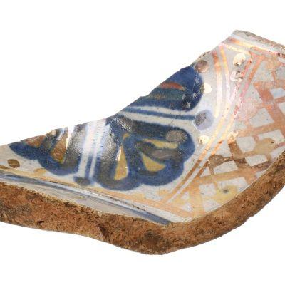 Sinisillä ja kullanvärisillä kuvioilla koristeltu vadin kappale.
