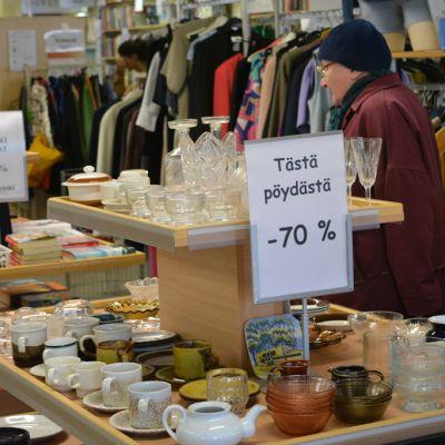 Asiakas katselee myyntipöydän tuotteita kierrätyskeskus Entringissä.