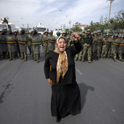 Uiguurivähemmistöön kuuluva nainen mellakkapoliisirivistön edessä.