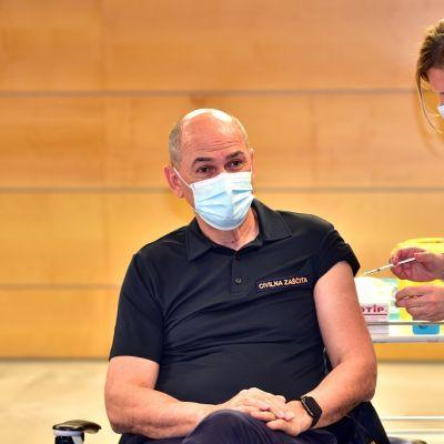Kuvassa hoitaja rokottaa Slovenian pääministerin Janez Janšan.