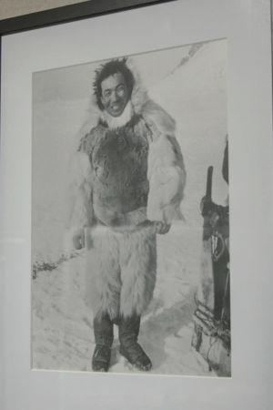 Mustavalkoinen arkistokuva kehyksissä, hymyilevä mies turkisasussa, taustalla lunta