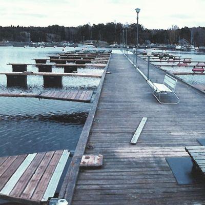 En lång brygga för småbåtar. På bryggan finns en bänk och i bakgrunden syns hus.