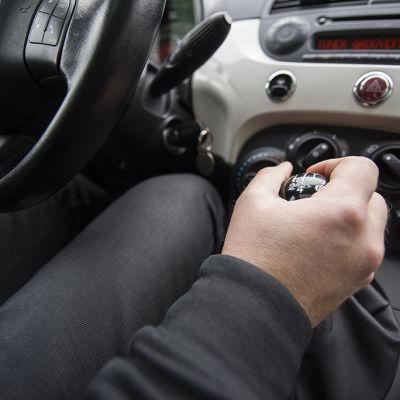 Henkilöauton kuljettaja pitää kiinni vaihdekepistä.