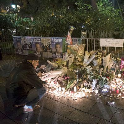 muistokynttilöitä ja kukkia kadulla
