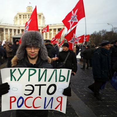 Karvalakkipäinen mies pitää lappua, jossa lukee kyrillisin kirjaimin: Kurily - eto rossija. Taustalla näkyy Vasemmistorintaman punaisia lippuja.