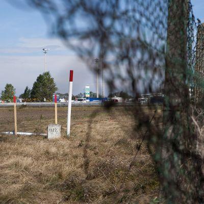 Tolppia ruohikkoisessa maassa, edessä ruostunut ja repaleinen verkkoaita.