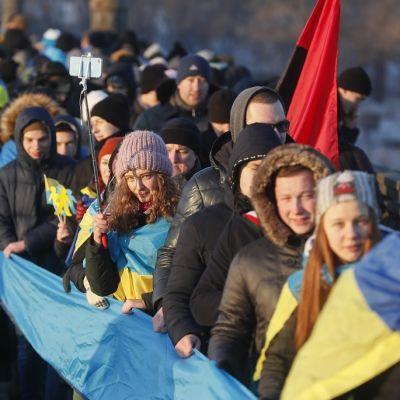 Joukko ihmisiä seisoo pitkässä jonossa ja pitelee Ukrainan lipun väreissä olevaa pitkää kangasta.