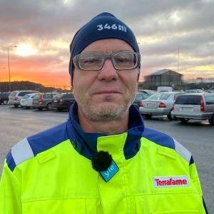 Jukka Vetola, huvudförtroendeman för arbetstagarna på Terrafame ser in i kameran. Han har på sig en gul rock och en blå mössa.