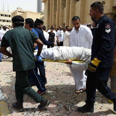 Pelastushenkilöstö kantaa iskussa loukkaantunutta ulos moskeijasta Kuwait Cityssä 26. kesäkuuta 2015.