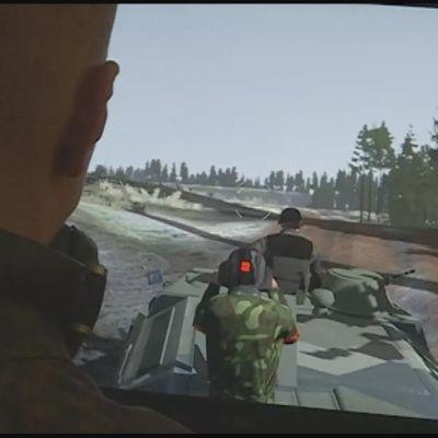 En man tittar på en skärm där det synns en pansarvagn och någon som skjuter.