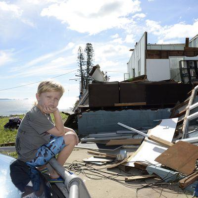 Seitsemänvuotias poika myrskyssä tuhoutuneen kotinsa edustalla Yeppoonin rantakaupungissa, Queenslandin osavaltiossa 21. helmikuuta.