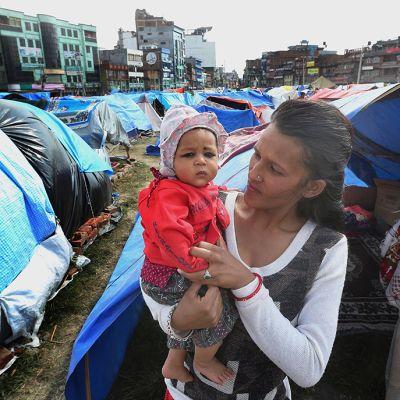 Äiti lapsensa kanssa väliaikaisessa telttaleirissä maanjäristyksen jälkeen Katmandussa.