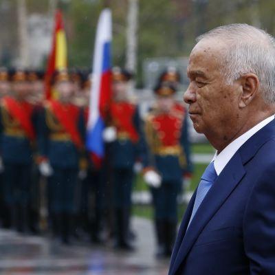 Sivuprofiili harmaantuneesta miehestä tummansinisessä puvussa. Taustalla lippuja piteleviä sotilaita.