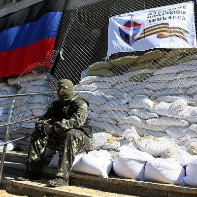 Naamioitunut venäläismielinen separatisti vallatun paikallishallinnon rakennuksen edustalla Slovjanskissa.