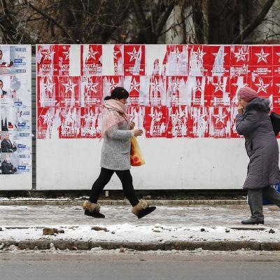 Kaksi naista kävelee vaalijulisteiden ohi talvisella kadulla.