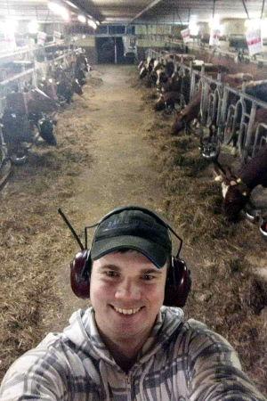 Kristoffer Nilsson som står framför en rad med kor, inne i en båsladugård.