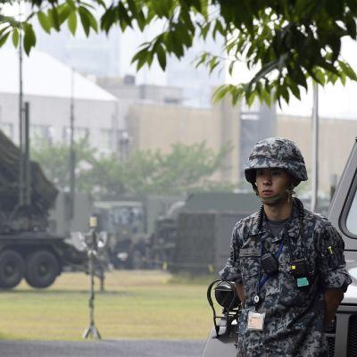 Maastopukuinen sotilas , taustalla sotilasajouneuvoja ja rakennuksia.