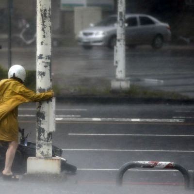 Keltaiseen sadetakkiin pukeutunut, puunrungosta pitelevä nainen yrittää nostaa mopedia sateisella kadulla.
