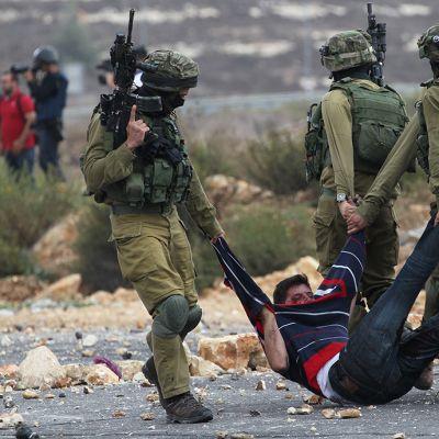Israelin sotilaat pidättivät palestiinalaisen miehen joka oli heittänyt kiviä Beit Elissä, lähellä Ramallahin kaupunkia 7. lokakuuta.