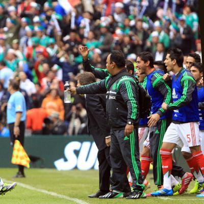 Meksikon Paul Aguilar ryntää vaihtopelaajien eteen juhlimaan maaliaan.