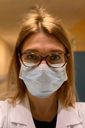 En läkare med andningsmask och glasögon.