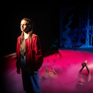 en ung kvinnlig skådespelare i förgrunden, armar sticker upp ur dimma på golvet