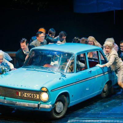 Lahden kaupunginteatterin näyttelijät työntävät Hillman-autoa.