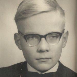 Pertti Simula lapsena silmälasit päässä, rusetti kaulassa.