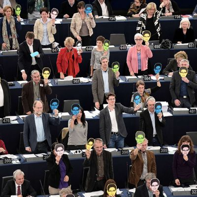 Eu parlamentin jäsenet nostavat Snowden-maskit ylös äänestäessään täysistunnossa Strasbourgissa keskiviikkona 12. maaliskuuta 2014.
