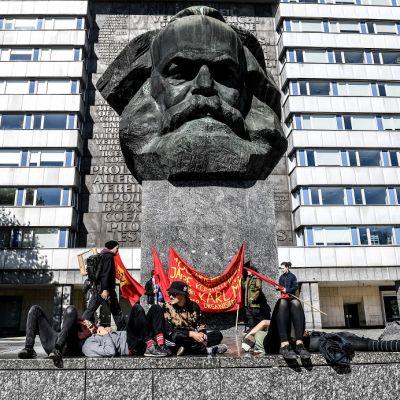 Pieni joukko nuoria ihmisiä punaisten banderollien kanssa makailee ja istuskelee jyhkeän betonisen Marxin päätä esittävän patsaan jalustan juurella. Taustalla vaalea DDR-tyylinen kerrostalo.