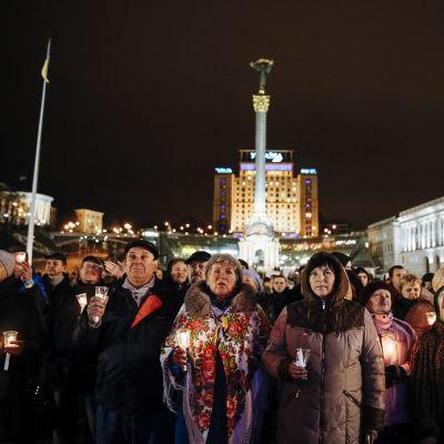 Ihmisiä kynttilät kädessä Maidanilla.