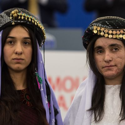 Nuoret naiset katsovat vakavina kameraan huivit päässä.