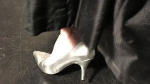 En högklackad silversko och en svart kjolfåll.
