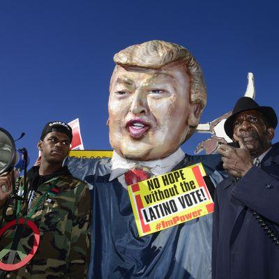 Donald Trumpia muistuttava pilanukke ja mielenosoittajia.