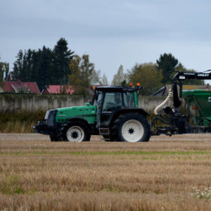 En grön traktor med släp sprider ut strukturkalk på en åker.