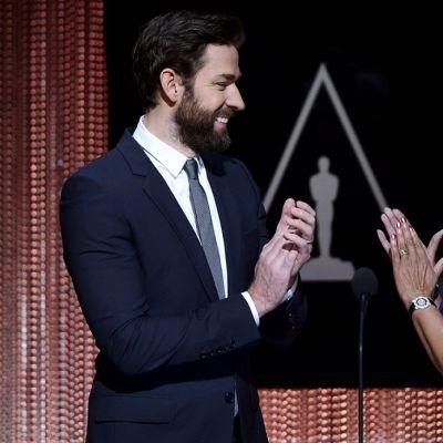 John Krasinski ja Cheryl Boone Isaacs katsovat toisiaan ja taputtavat käsiään teatterilavalla. Taustalla elokuva-akatemian logo.