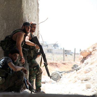 Kuvassa maastoasuisia sotilaita, joilla aseet.
