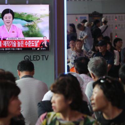 Eteläkorealaiset katsovat televisiota, jossa näkyy pohjoiskorealainen uutisankkuri vaaleanpunaisessa asussa.