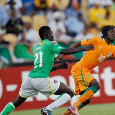 Norsunluurannikon Gervinho (oik.) tavoittelee korkeaa palloa. Togon Dakonam Djene (vas.) seuraa.