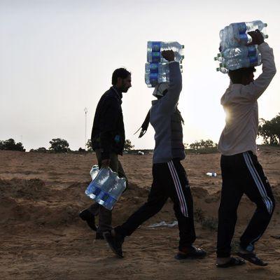 Ihmiset kantavat vettä pakolaisleirillä Tunisiassa maaliskuussa 2011.