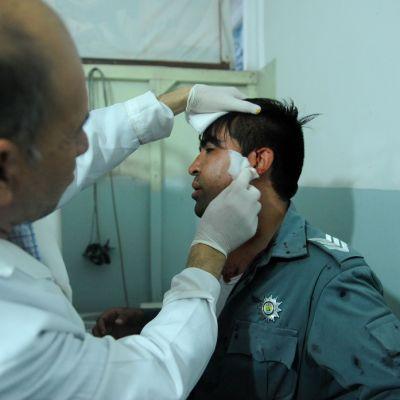Lääkäri hoitaa verta vuotavaa miestä, jolla on univormu yllään.