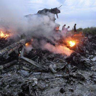 Vielä tulessa oleva koneen runko maassa.